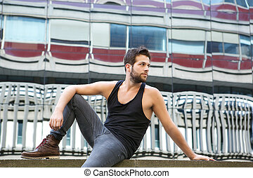 Male fashion model sitting outdoors in urban area