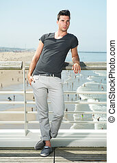 Male fashion model standing at beach