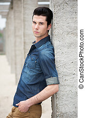 Male fashion model standing outdoors
