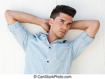 Male fashion model with arms raised behind head