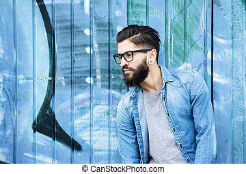 Portrait of a male fashion model with beard and glasses standing against graffiti background