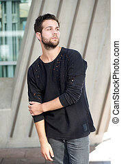 Male fashion model with beard posing outdoors