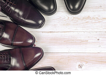 Male fashion with shoes on wooden background.