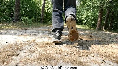 Male feet in black sneakers start running in a forest in...