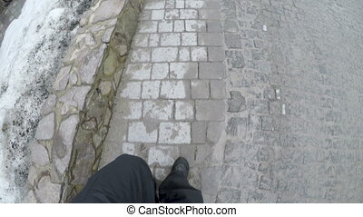 male feet in shoes go on paving stones in winter