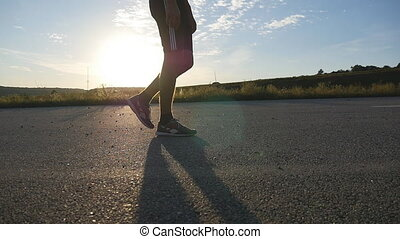 Male feet is walking on a rural road at sunset, close up....