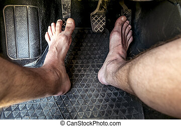 Male feet on the brake and accelerator pedals in a car