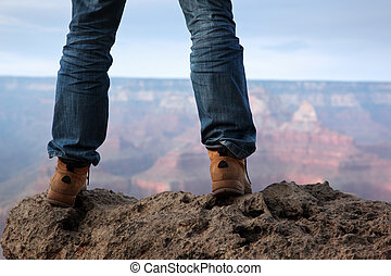 Male feet standing on edge of a cliff - Man in hiking boots...