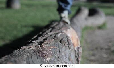 Male feet walk on a log