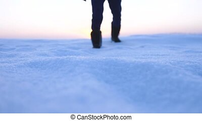 Male feet walking in deep snow. foot steps of hiker. recreational winter activity outdoors