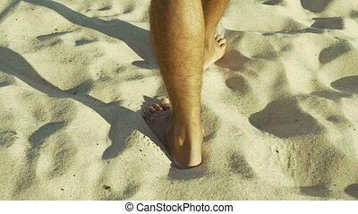 Male feet walking on sand. Tanned man in khaki shorts...