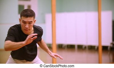 Male fighter performs martial tricks in the sport gym....