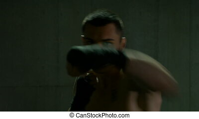 Male fighter warming up and exercising box moves at training...