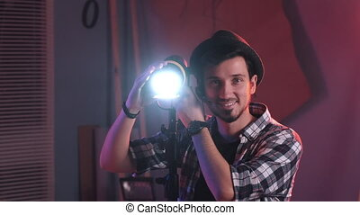 Close-up shot of Male filmmaker adjusting professional light stand in studioand smiling to the camera. There is red light in film studio.