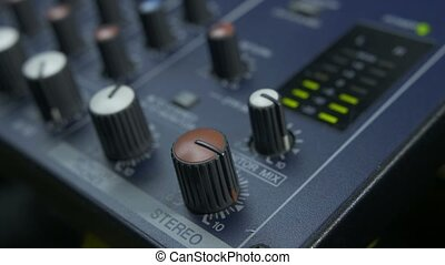 Male fingers turning fader knob on audio mixer - Close-up of...