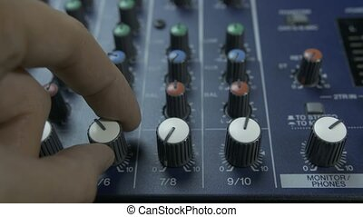 Male fingers turning knobs on audio mixing desk