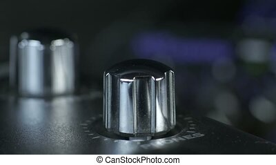 Close-up of male fingers turning shiny silver metal audio interface knob.