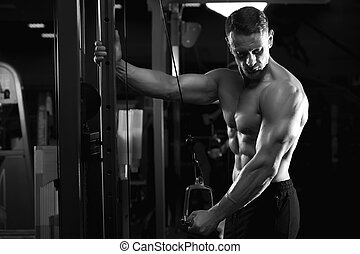 Male fitness model working out in gym