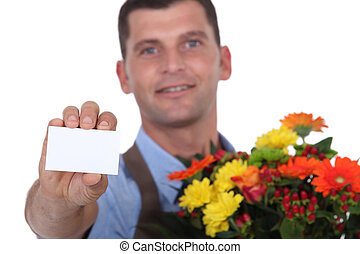 Male florist holding a blank business card