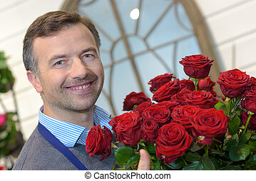 male florist holding a pot of red roses