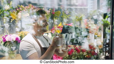 Male florist in apron changing closed sign to open on flower...