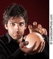 Male Fortune Teller - Serious fortune teller holds crystal...