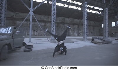Male free runner jumping over car and doing parkour tricks in an abandoned building. Guy showing acrobatic stunts and somersaulting indoor. Concept of sportive lifestyle. Side view Close up Slow motion.