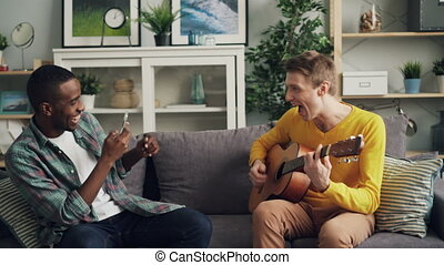 Male friends are having fun at home, Caucasian guy is playing the guitar and African American young man is recording video with smartphone. Friendship and music concept.