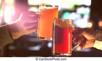 Male friends clinking with beer mugs in pub. Beer mugs of...