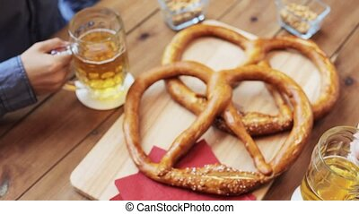 people, men, leisure, friendship and communication concept - two male friends drinking beer and clinking glasses with pretzels on table at bar or pub
