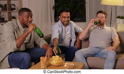 male friends drinking beer with crisps at home