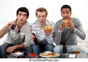 Male friends eating burgers and watching sport on TV