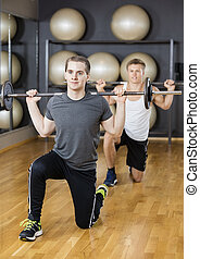 Male Friends Lifting Barbell In Gym