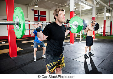 Male Friends Lifting Barbells In Fitness Center