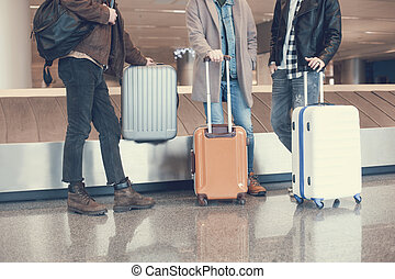 Male friends locating with baggages in airport