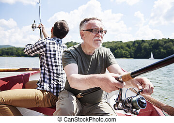 Male friendship with fishing rod on the rowboat