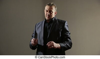 male gangster in a business suit with a knife. shaves his cheeks.