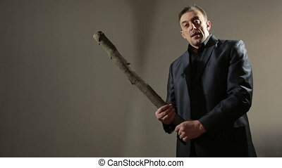 male gangster with bat. a man in a business suit threatening...