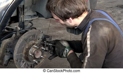 male garage worker repair car brake system at work.