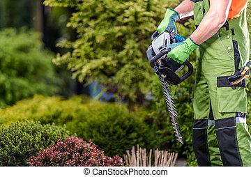Male Gardener Holding Gasoline Garden Trimmer.