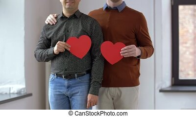 male gay couple with red heart shapes at home
