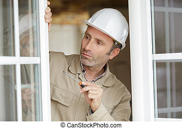 male glazier holding screwdriver by open pvc window