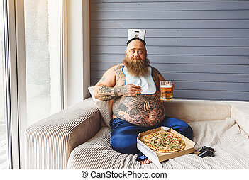 Male glutton eating junk food with alcohol
