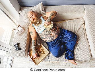 Male glutton enjoying unhealthy food