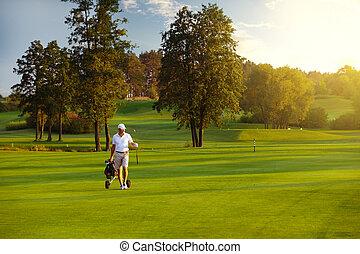 male golf player - Handsome man golfer walking on fairway at...