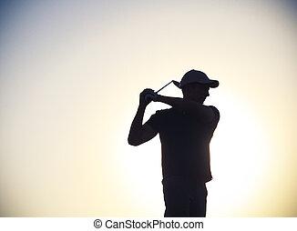 Male golfer at sunset