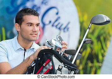 male golfer choosing a club from his bag