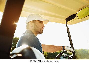 Male golfer driving a golf cart