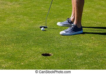 Male golfer feet next to hole