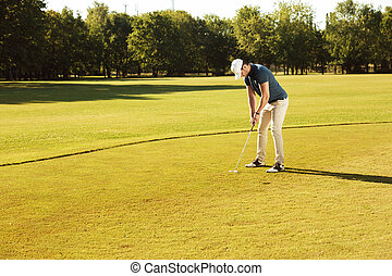 Male golfer putting golf ball on green